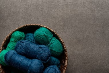 top view of green and blue yarn clews in wicker basket on grey background