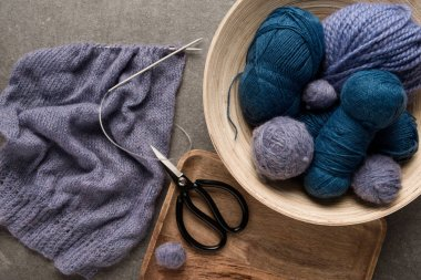 flat lay with purple and blue yarn balls with scissors and knitting needles on grey background