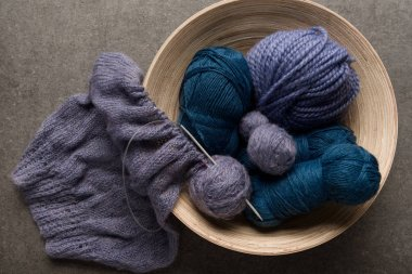 flat lay with purple and blue yarn balls in bowl on grey background