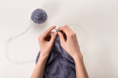partial view of woman knitting yarn on grey backdrop