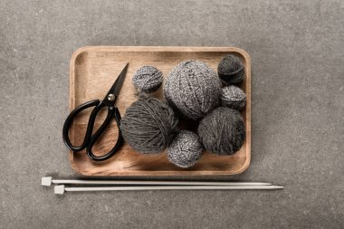 top view of grey knitting, scissors and knitting needles on grey background