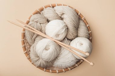 top view of yarn and knitting needles in wicker basket on beige background