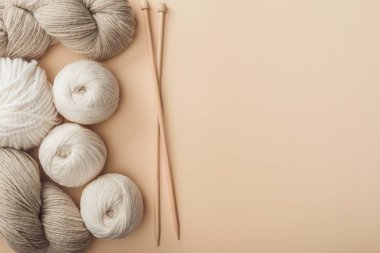 flat lay with yarn and knitting needles on beige backdrop