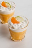 Photo orange cream desserts with tangerine and lime slices in glasses