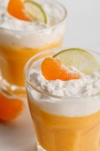 Photo close up of glasses with orange mousse with tangerine and lime slices