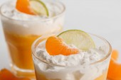 close up of two glasses of cream desserts with tangerine and lime slices