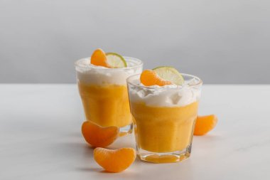two glasses with cream desserts with tangerine and lime slices
