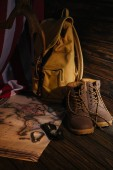 close-up view of trekking boots, hiking equipment, map, backpack and american flag on wooden surface