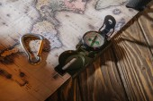 Fotografie Detailní zobrazení kompasu, závěsného oka a mapu na dřevěný stůl