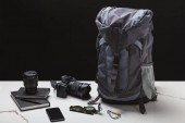 Fotografie backpack, smartphone, compass, notebooks and photo camera with lens on black