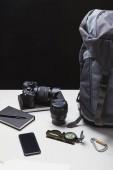 Fotografie batoh, smartphone, fotoaparát s objektivem a sledování zařízení
