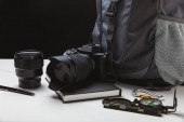 close up view of photo camera with lens, pen, notebook, compass and backpack on black