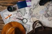 barna bőr táska, kalap, nagyító, kis modell repülőgép, fényképezőgép, objektív és útlevél Beszállókártyával térképen felülnézetben