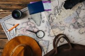 Fotografie top view of brown leather bag, hat, magnifying glass, small model plane, earphones, photo camera, lens and passport with boarding pass on map