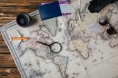 Nagyító, kis modell repülőgép, napszemüveg, fényképezőgép, objektív és útlevél Beszállókártyával térképen felülnézetben