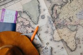 pohled shora pasu s palubní vstupenku, klobouk, sluchátka a malé letadlo model v mapě
