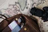 Fotografie pohled shora kožená brašna s pas, letenku, sluneční brýle, fotoaparát a mapa