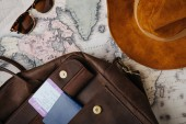Fotografie top view of leather bag, passport, ticket, sunglasses, hat and map