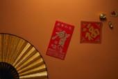 felülnézet rajongó hieroglifák és a barna háttér, kínai új év összetétele arany díszek