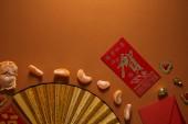 pohled shora oloupané mandarinky, ventilátor s hieroglyfy a červenou obálku na hnědé pozadí
