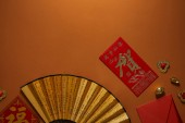 Photo top view of chinese new year composition with golden decorations and fan with hieroglyphs on brown background