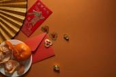 pohled shora mandarinky na talíř, ventilátor s hieroglyfy, zlaté dekorace a červenou obálku na hnědé pozadí, čínský Nový rok složení