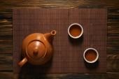 Fotografie pohled shora hnědá keramická konvice a šálky čaje na bambusové rohoži