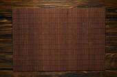 Draufsicht auf leere braune Bambusmatte auf Holztisch