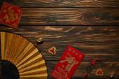 pohled shora na čínský Nový rok složení s ventilátorem, hieroglyfy a ozdobné zlaté mince na dřevěný povrch