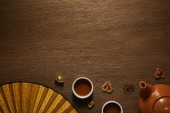 Photo top view of tea set, fan with hieroglyphs and golden coins on wooden surface