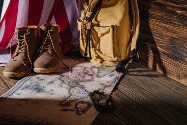 trekking boots, hiking equipment, map, backpack and american flag on wooden surface