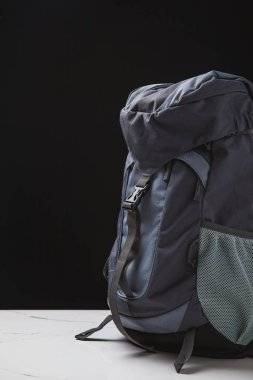 close-up view of backpack for hiking on black background, travel concept