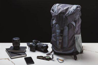 backpack, smartphone, compass, notebooks and photo camera with lens on black