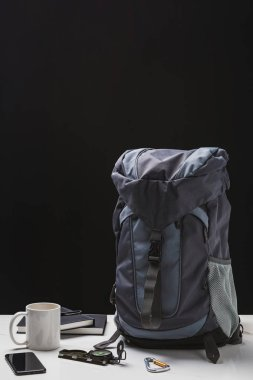 backpack, cup, notebooks, smartphone and trekking equipment on black