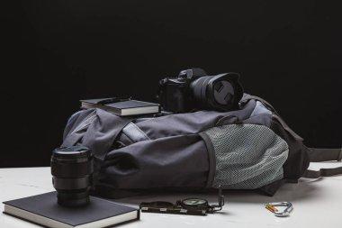backpack, photo camera and trekking equipment on black