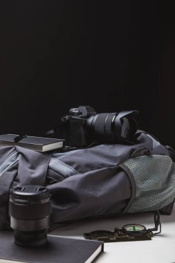 backpack, photo camera with lens, notebooks with pen and compass on black, travel concept