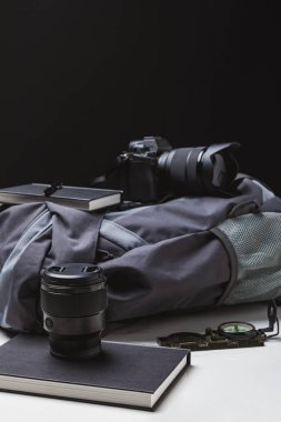 backpack, photo camera with lens, notebooks with pen and compass on black