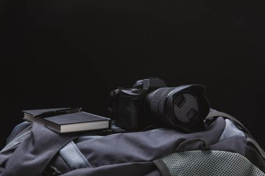 close-up view of photo camera with notebook and pen on backpack isolated on black