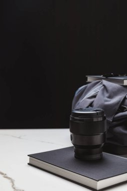 close-up view of photo lens on notebook and backpack on black