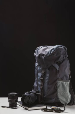 backpack, photo camera with lens, notebook and trekking equipment on black