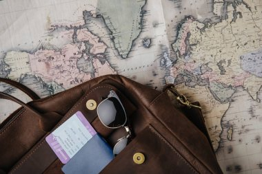 top view of leather bag with passport, ticket, sunglasses and map. travel concept