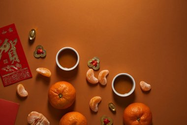 top view of tea cups, tangerines and traditional chinese decorations on brown background