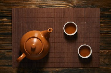 top view of brown ceramic teapot and cups of tea on bamboo mat