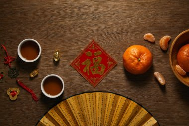 Fan, fresh ripe tangerines, golden hieroglyph, cups of tea and coins on wooden surface stock vector