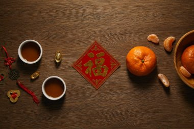 Top view of fresh ripe tangerines, golden hieroglyph, cups of tea and coins on wooden surface stock vector