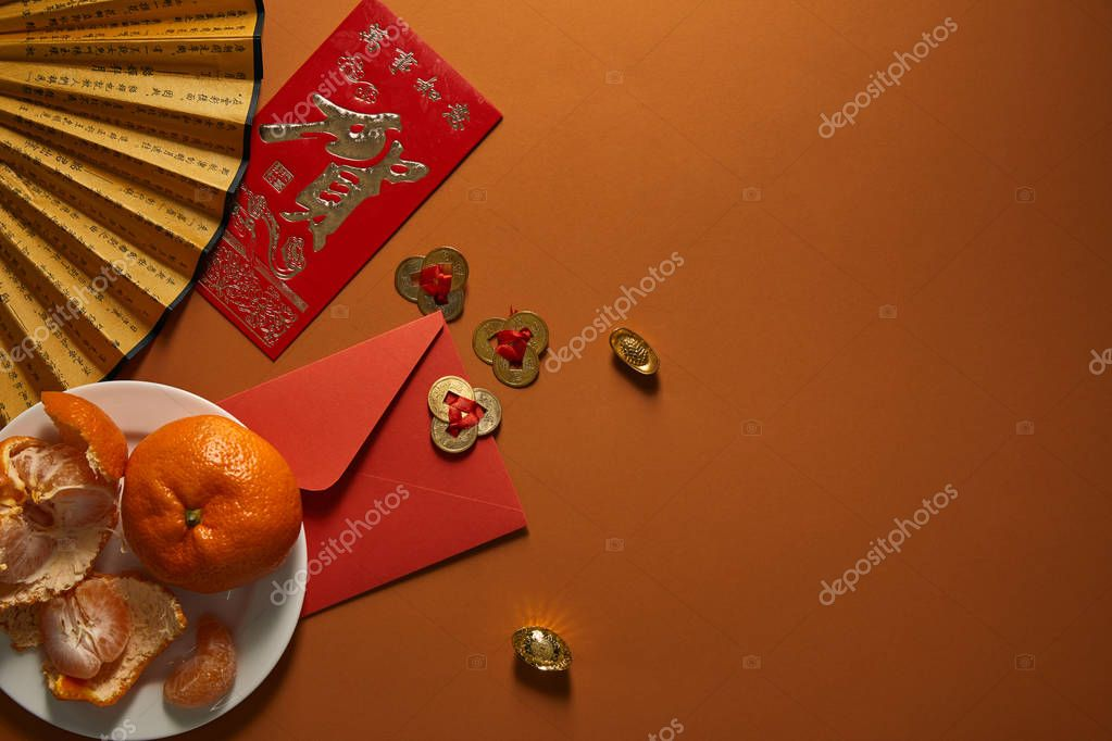 top view of tangerines on plate, fan with hieroglyphs, golden decorations and red envelope on brown background, chinese new year composition