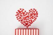 Fotografie Draufsicht der herzförmigen Anordnung der kleinen roten Papier schneiden, Herzen und gestreiften Geschenkbox auf weißem Hintergrund