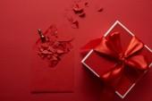 Fotografie pohled shora Dárková krabice se saténovou stuhou a papír vyjmout srdce s obálkou na červeném pozadí