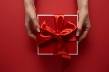 partial view of female hands holding present with silk ribbon on red background