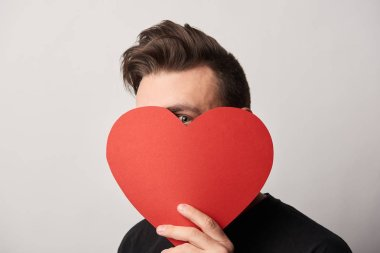 man with obscure face holding empty paper cut heart card and looking at camera